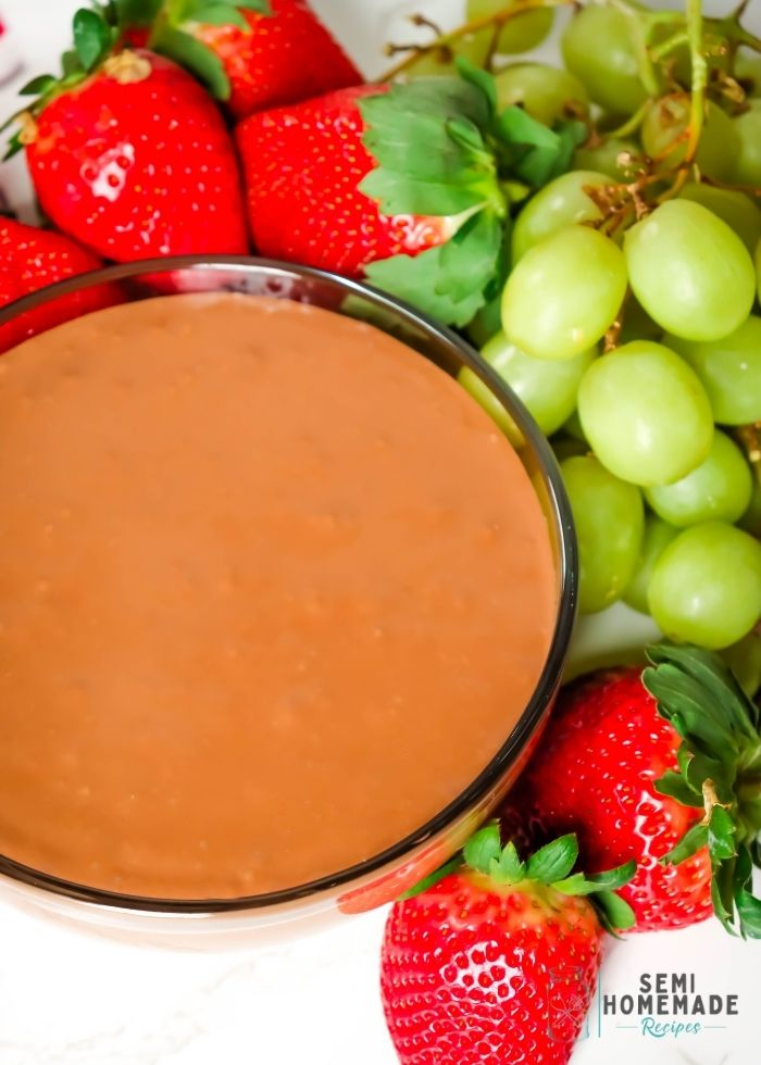 NUTELLA MARSHMALLOW DIP in a bowl surrounded by green grapes and red strawberries