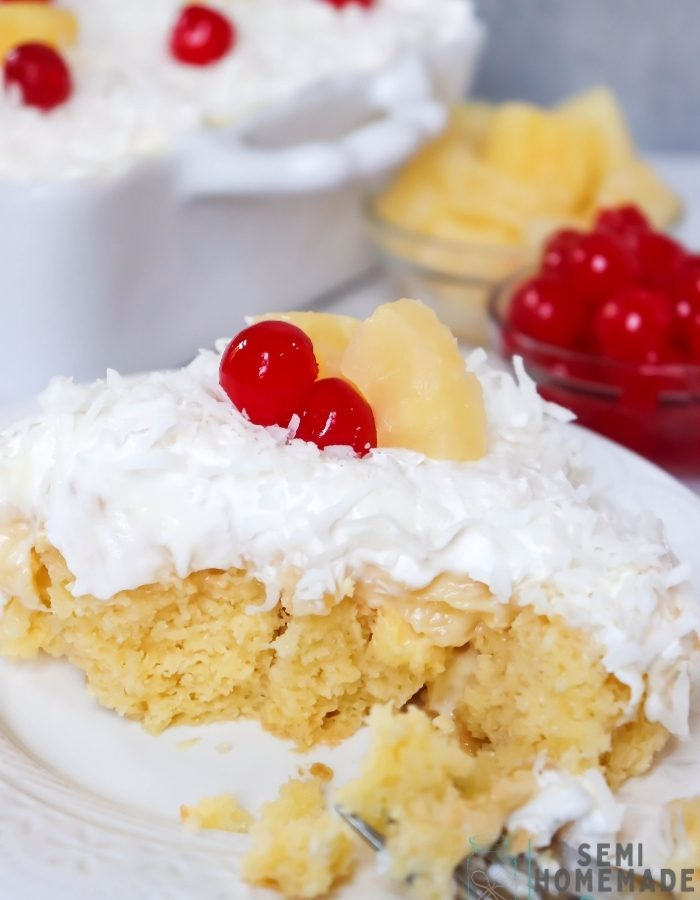 Bite missing from PINA COLADA POKE CAKE on white plate