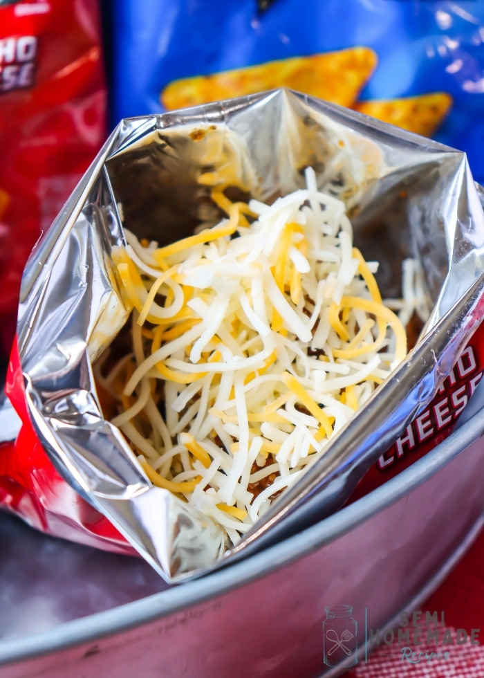 adding cheese to adding cooked beef to crushed Open Bag of Doritos