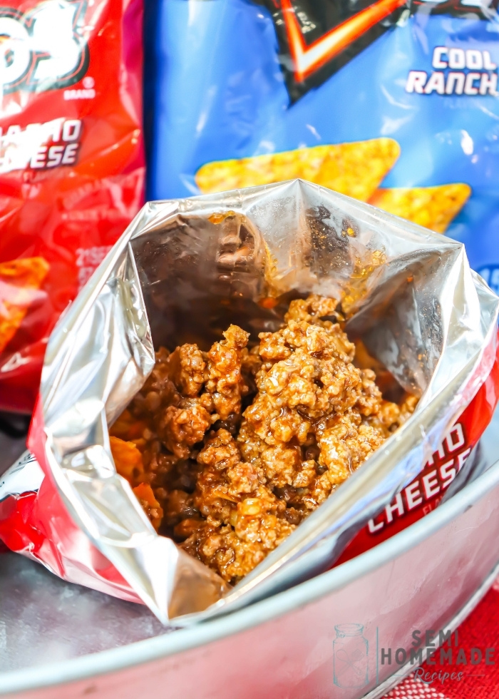 adding cooked beef to crushed Open Bag of Doritos
