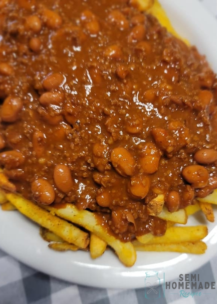 fries topped with chili and beans on white plate