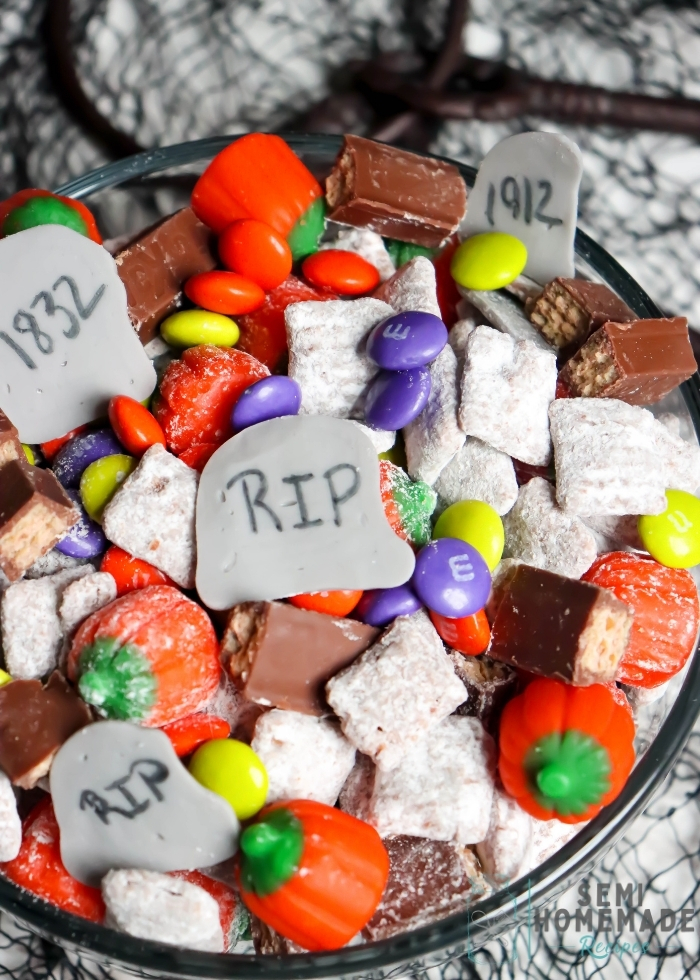 This Grave Yard Snack Mix is made with homemade muddie buddy chex mix, candy pumpkins, Halloween M&Ms, Kit Kats and homemade candy tombstones.